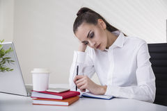 Stående av en fundersam brun haired affärskvinna i ett vitt blussammanträde på hennes tabell i ett kontor fotografering för bildbyråer