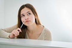 Stående av en fundersam tonårs- flicka på skrivbordet Royaltyfria Foton