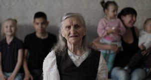 Stående av en gammal grå hårfarmor med en stor familj stock video