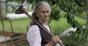 Stående av en gammal kvinna med en hacka på hennes skuldra stock video