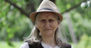 Stående av en gammal kvinna med långt grått hår i en sugrörhatt utomhus arkivfilmer