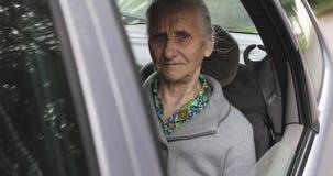 Stående av en gammal kvinna med skrynklor i ett öppet bilfönster stock video