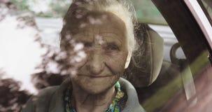 Stående av en gammal kvinna med skrynklor till och med ett bilfönster lager videofilmer
