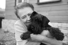 Stående av en gammal kvinna som rymmer den svarta hunden Arkivbild