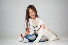 Stående av en glad liten flicka som har gyckel med den siberian skrovliga valpen på golvet på studion arkivbild