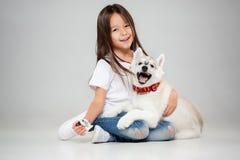 Stående av en glad liten flicka som har gyckel med den siberian skrovliga valpen på golvet på studion royaltyfria foton