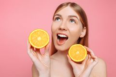 Stående av en gladlynt kvinnlig flicka, naturlig klar hud, flicka med två orange skivor som isoleras på en rosa bakgrund fotografering för bildbyråer