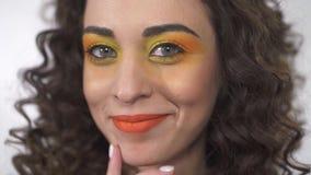Stående av en gladlynt le flicka med lockigt hår och det ljusa makeupanseendet på en vit bakgrund i studion arkivfilmer