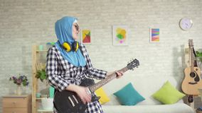 Stående av en gladlynt muslim ung kvinna i hijab som hemma spelar en elektrisk gitarr lager videofilmer