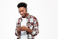 Stående av en gladlynt ung afro amerikansk man i hörlurar arkivfoton