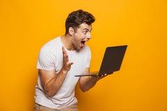 Stående av en gladlynt ung man som använder bärbar datordatoren arkivbilder