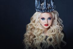 Stående av en gotisk prinsessa Härlig ung blond kvinna i metallkrona och svart kappa arkivbild