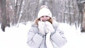 Stående av en gullig flicka i vintern under snöfall lager videofilmer