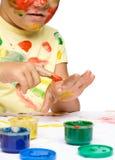 Stående av en gullig flicka som spelar med målarfärger royaltyfri fotografi