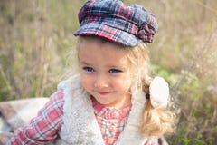 Stående av en gullig gladlynt liten flicka på en natur Arkivbilder