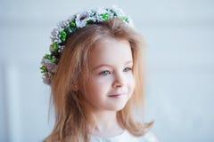 Stående av en gullig liten flicka i krans av blommor Arkivfoton