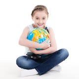 Stående av en gullig liten flicka med ett jordklot. Arkivfoton