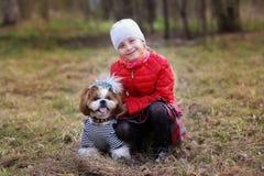 Stående av en gullig liten flicka med hennes älsklings- hund arkivfoto