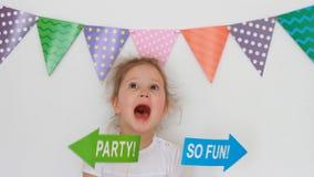 Stående av en gullig liten flicka på en ljus bakgrund med kulöra flaggor och dekoren för att fira en lycklig födelsedag _ stock video