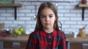 Stående av en gullig liten le flicka i ett rutigt skjortaanseende i köket arkivfilmer