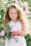Stående av en gullig litet barnflicka som är utomhus- i en rosträdgård som luktar blommorna Royaltyfri Bild