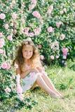 Stående av en gullig litet barnflicka som är utomhus- i ett rosträdgårdsammanträde under buskarna Royaltyfri Foto