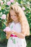 Stående av en gullig litet barnflicka som är utomhus- i trädgården som luktar de rosa rosorna Royaltyfri Bild