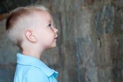 Stående av en gullig pojke nära en tegelstenvägg Royaltyfri Bild