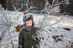 Stående av en gullig pys i varm kläder som utomhus spelar under snöfall i solig dag för vinter royaltyfria bilder