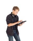 Stående av en gullig tonårs- pojke med hörlurar och tabletdatoren. Fotografering för Bildbyråer