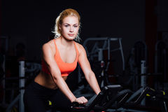 Stående av en gullig trevlig kvinnlig genomkörare på kondition motionscykelmörkret på idrottshallen Royaltyfri Foto