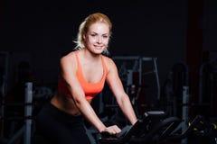 Stående av en gullig trevlig kvinnlig genomkörare på kondition motionscykelmörkret på idrottshallen Royaltyfri Fotografi