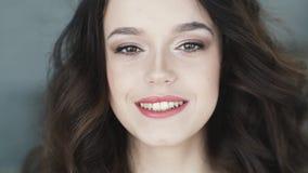 Stående av en gullig ung brunett med bruna ögon Flickan ser och ler hemskt på kameran långsam rörelse lager videofilmer