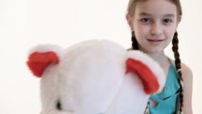 Stående av en gullig vit flicka med råttsvansar som kramar med en stor nallebjörn som in sitter på golvet på en vit bakgrund lager videofilmer