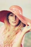 Stående av en härlig behagfull kvinna i elegant rosa hatt med ett brett brätte kvinna för silhouette för symbol för skönhetbegrep Arkivbilder