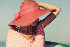 Stående av en härlig behagfull kvinna i elegant rosa hatt med ett brett brätte kvinna för silhouette för symbol för skönhetbegrep Royaltyfria Bilder