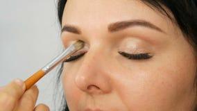 Stående av en härlig blåögd kvinnamodell med långt svart hår som gör makeup och ögonbrynet för aftonbruntöga lager videofilmer