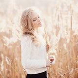 Stående av en härlig blond flicka i ett fält i den vita sweatern som ler med stängda ögon, begreppsskönhet och hälsa Royaltyfria Bilder