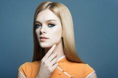 Stående av en härlig blond flicka i studion på en blå bakgrund, begreppet av hälsa och skönhet Royaltyfria Bilder