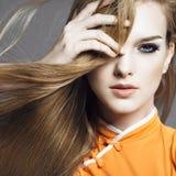 Stående av en härlig blond flicka i studion på en grå bakgrund med framkallande hår, begreppet av hälsa och skönhet Royaltyfri Foto