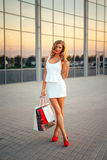 Stående av en härlig blond flicka med shopping Royaltyfri Bild