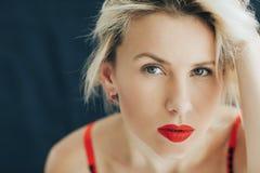 Stående av en härlig blond kvinna i en röd läppstift på hennes kanter arkivfoton