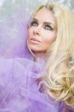 Stående av en härlig blond kvinna med långt lockigt hår, som sitter bak det glass fönstret som slås in i en purpurfärgad tyll Fotografering för Bildbyråer