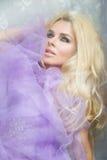Stående av en härlig blond kvinna med långt lockigt hår, som sitter bak det glass fönstret som slås in i en purpurfärgad tyll Arkivfoton