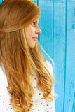 Stående av en härlig blond tonårs- flicka på en blå vägg royaltyfria bilder