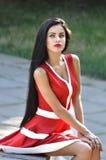 Stående av en härlig brunett i en röd klänning Arkivbilder