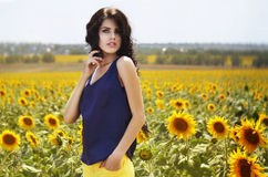 Stående av en härlig brunett i ett fält av solrosor Royaltyfria Bilder