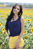Stående av en härlig brunett i ett fält av solrosor Royaltyfri Foto