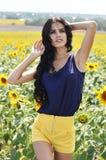 Stående av en härlig brunett i ett fält av solrosor Royaltyfria Foton