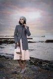 Stående av en härlig brunhårig kvinna på bakgrunden av havet Arkivfoto